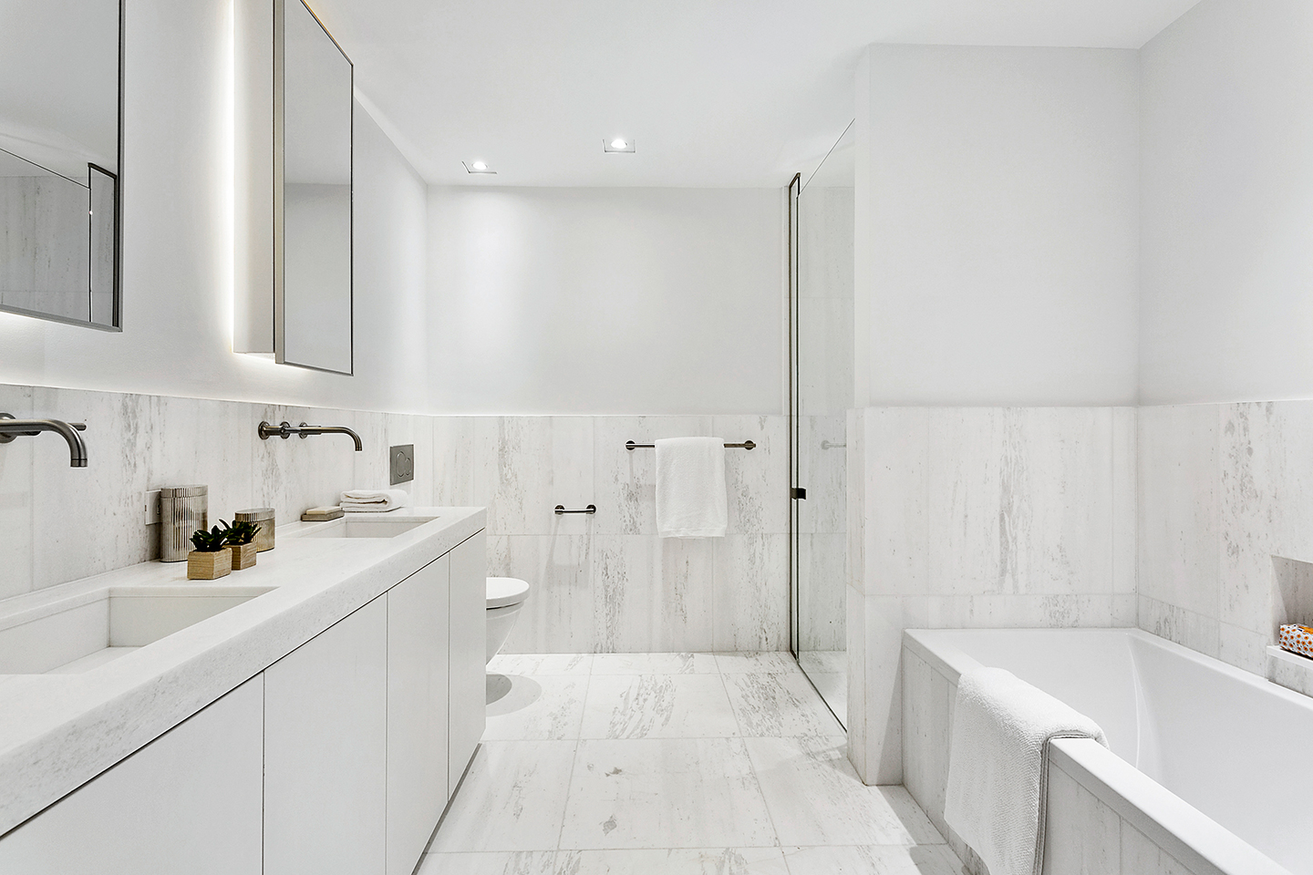Finely honed marble countertops and wall cladding in the master bathroom by Piet Boon