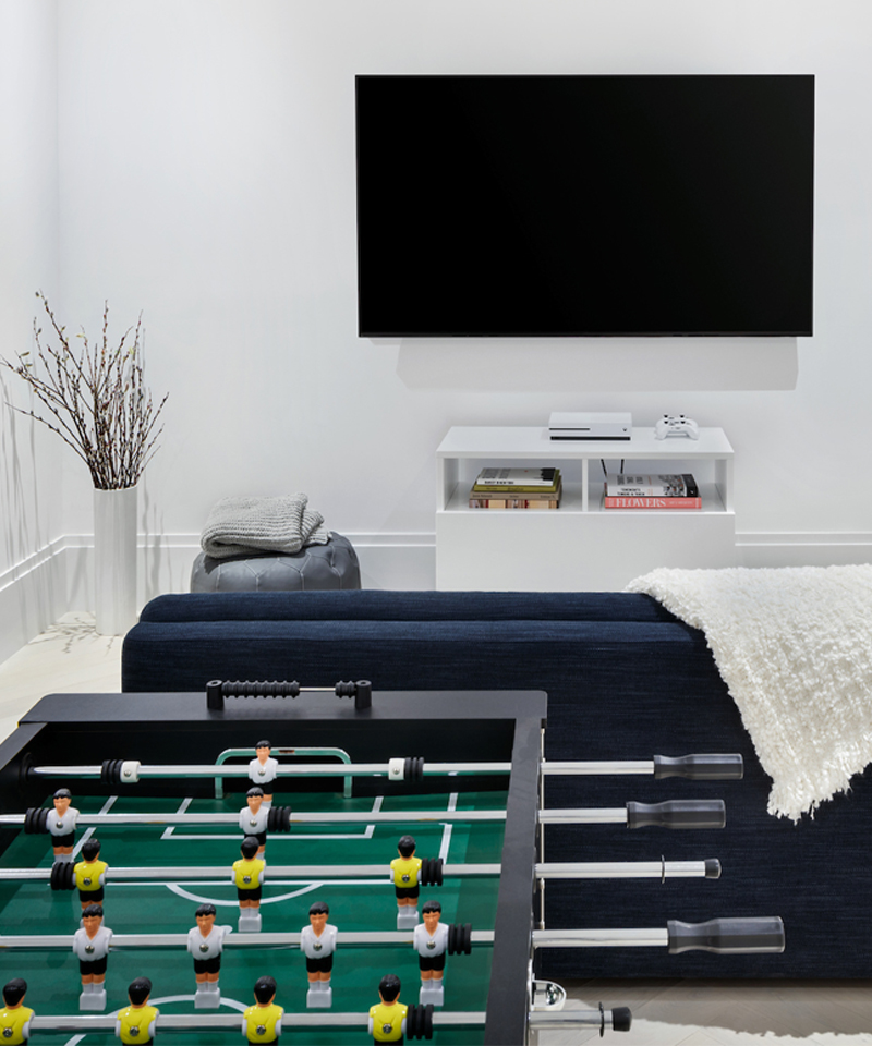 A game room includes a Foosball table and gaming station for residents who are young or young at heart.